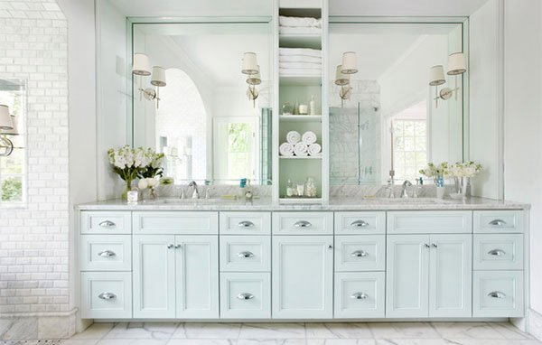 bathroom with light green cabinets and middle shelf divider