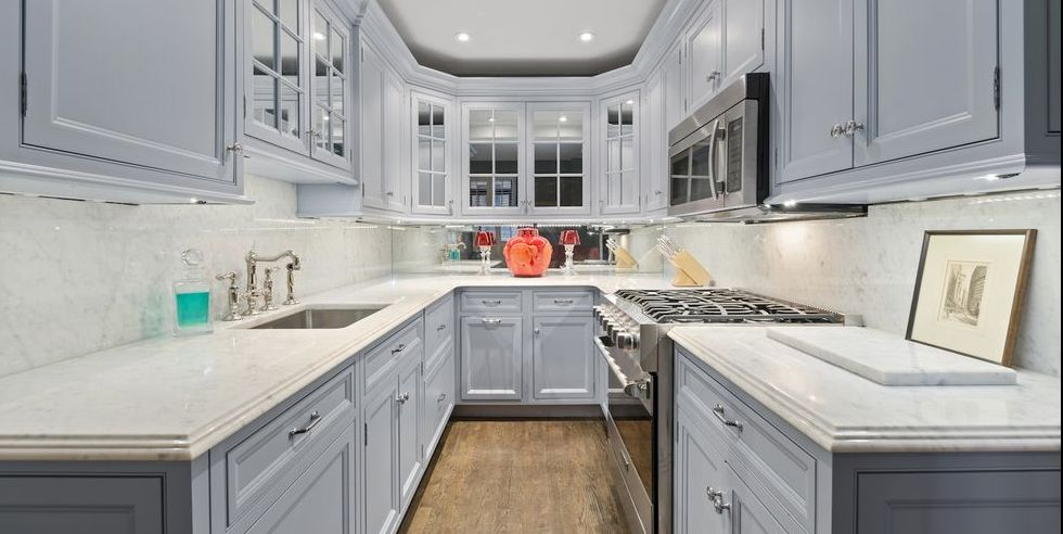 Stylish Small Kitchens, mirrored backsplash and light colored cabinets give the elusion of a bigger space