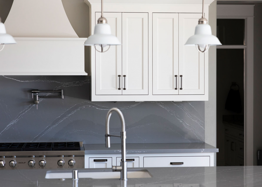 shaker style cabinet doors with a gray marble backsplash