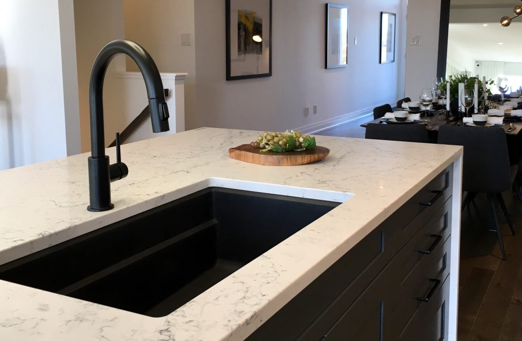 matte black kitchen faucet with a white marble waterfall countertop.