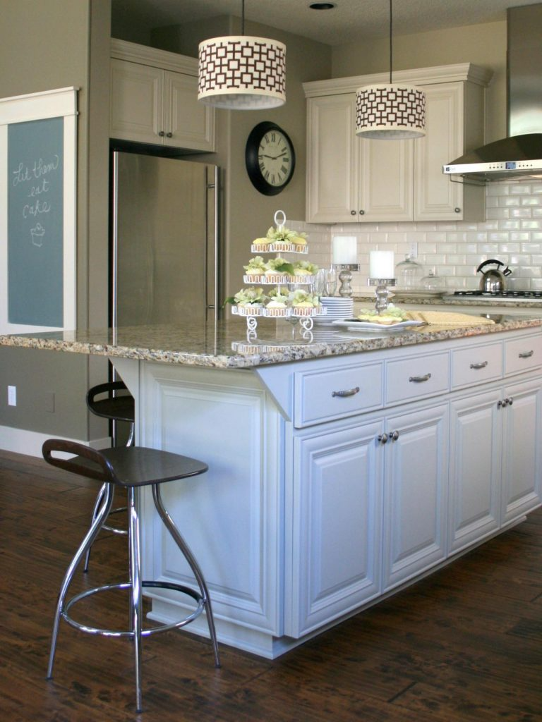 white kitchen cabinets with marble countertop with overhang