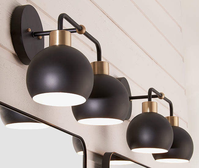 rounded matte black sconces over bathroom sinks and mirrors