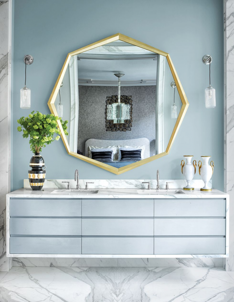 large geometric mirror above bathroom cabinets and sinks