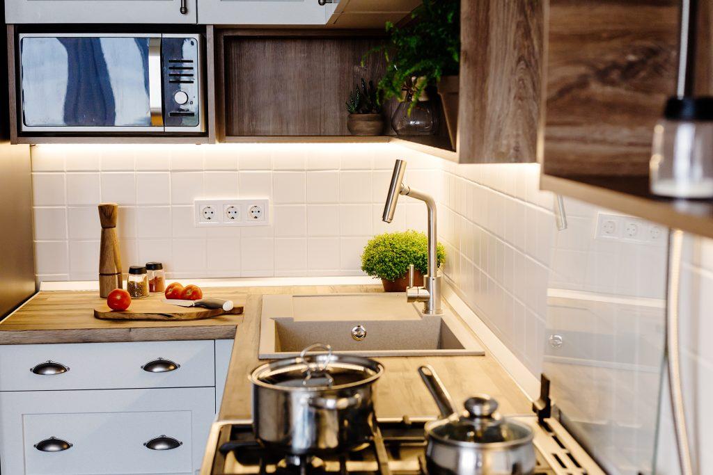 Modern Kitchen design in scandinavian style. stylish light grey kitchen interior with modern furniture and stainless steel appliances. wooden countertop, steel stove, under cabinet lighting