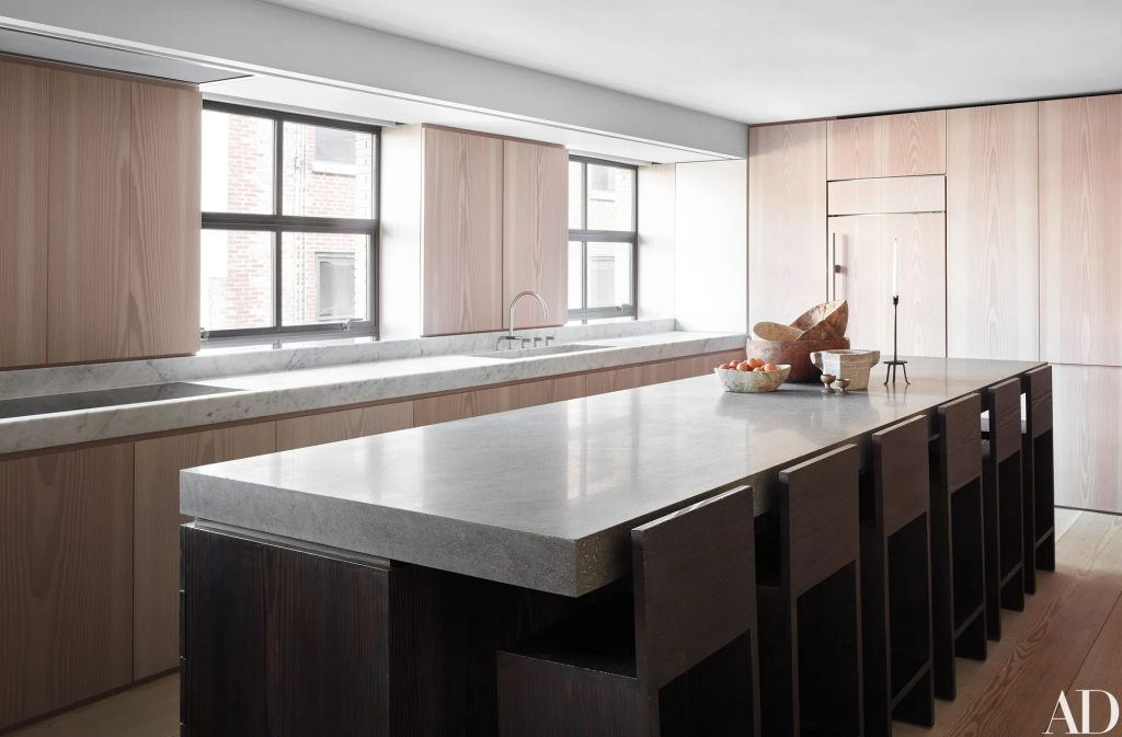 minimalist kitchen island with a cement counter and dark wood cabinets, stools with backs