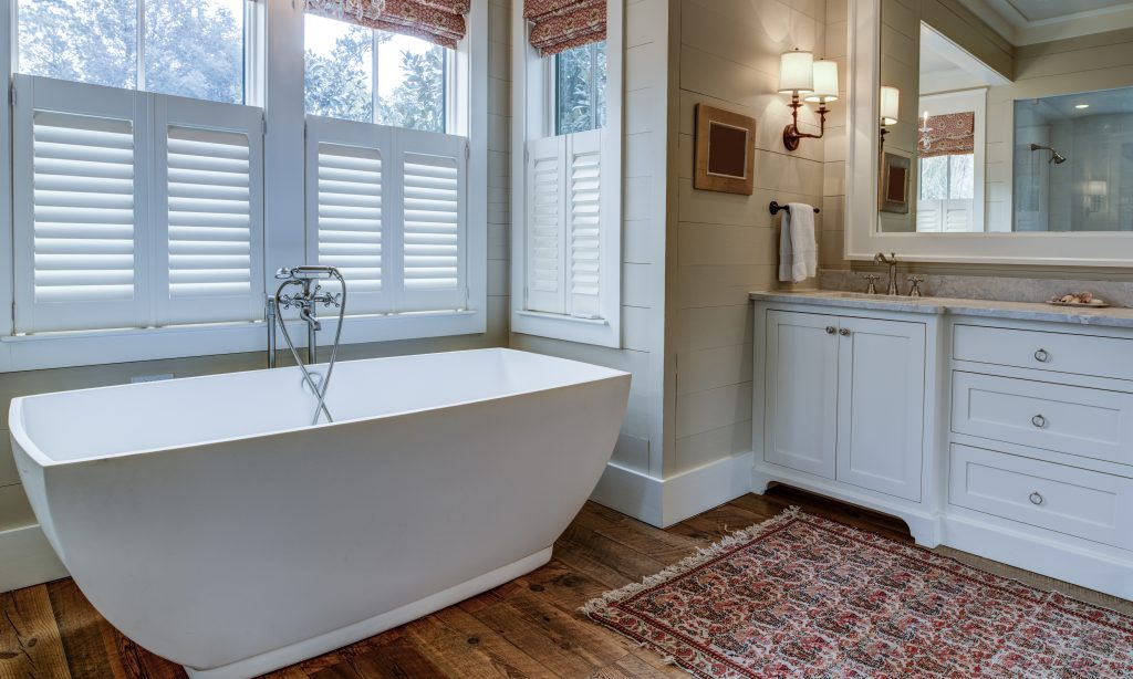 Luxury bathroom with large white tub, beautiful cabinets, and shiplap walls.