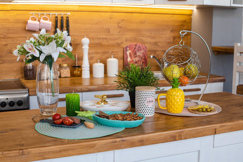 View over wooden counter set with snacks, lily flowers, fresh fruit in basket.