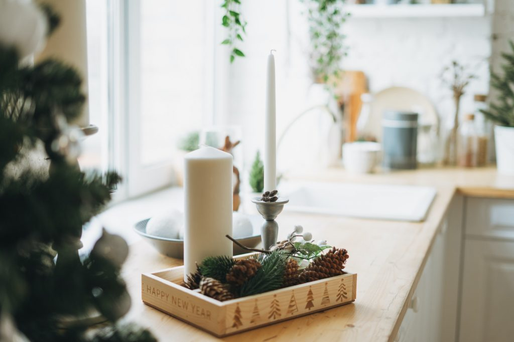 Christmas composition of white candles, pine branches and cones on the kitchen corner