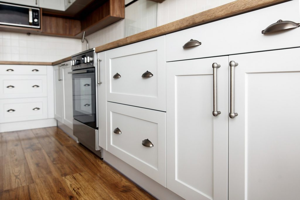 customize cabinet hardware by matching the style to your cabinets. These silver pulls and handles on white cabinets are a great example.
