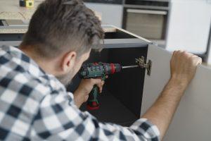 Man installing hinges in kitchen furniture
