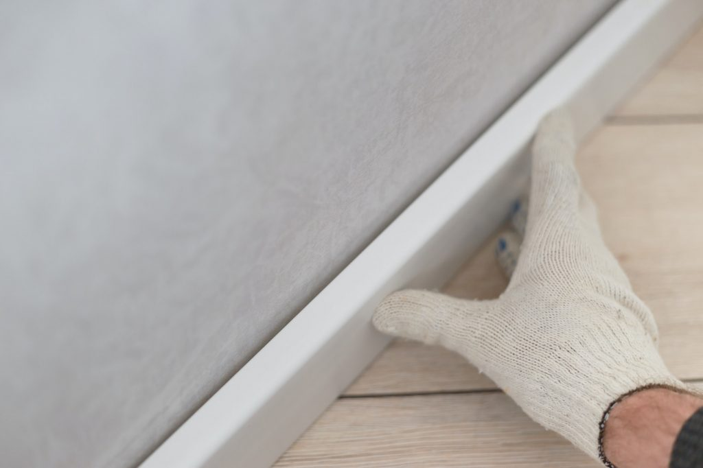 Man putting new skirting board on wall in house