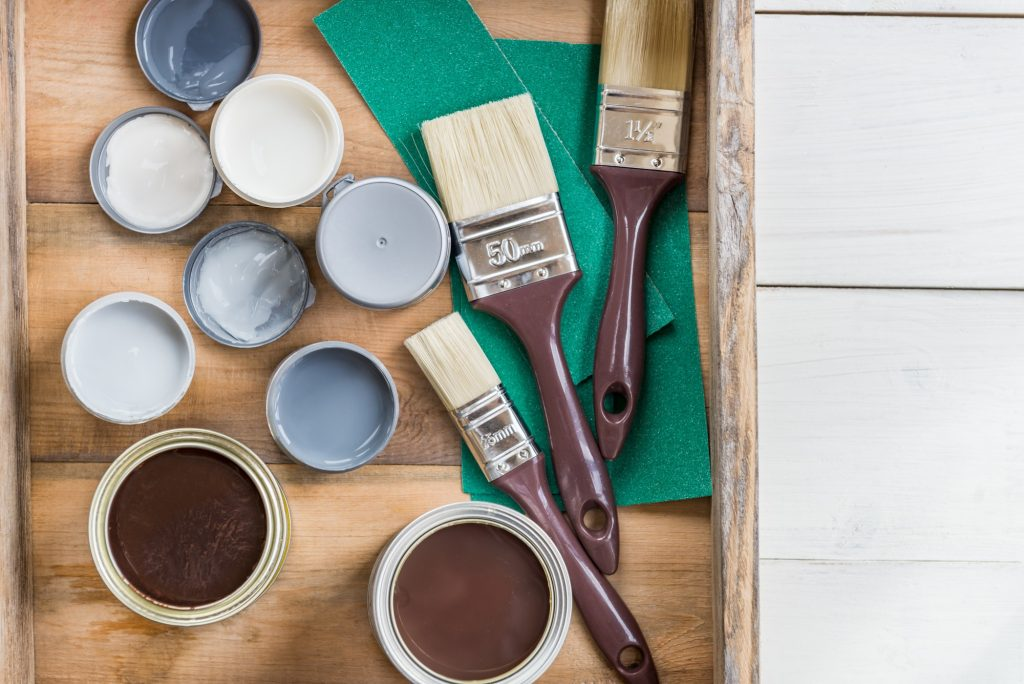paint brushes and cans of paint