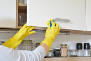 woman in yellow gloves washes the door in kitchen cabinet